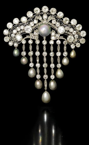 A belle époque natural pearl and diamond stomacher, circa 1910 The pierced and openwork surmount reminiscent of a Moorish archway, millegrain-set throughout with old brilliant and rose-cut diamonds, with a large natural pearl of pinkish/greyish tint at the centre, suspending a highly articulated fringe of triangular outline, set with similarly cut diamonds, each terminating in a drop-shaped grey pearl, mounted in platinum, diamonds approximately 11.20 carats total.