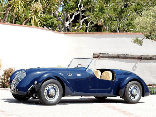 1949 Austin Healey Silverstone.   In a witty and practical touch, the spare tire protrudes from a horizontal opening in the rear body work, such that the protruding tire is the rear bumper.  The engine is a 2.4L, double over-head cam four, with dual, vacuum slide carburetors. Coach work is aluminum.