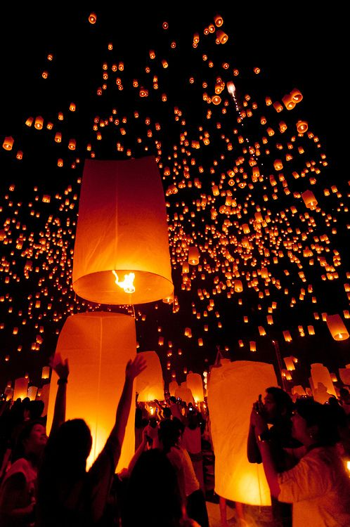 A young woman releases one of an estimated 10,000 floating lanterns during the annual Yee Peng Festival at the Lanna Dhutanka Buddhist Center near Chiang Mai, Thailand