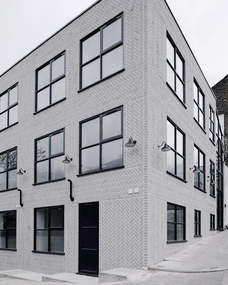Pale grey herringbone brick exterior, black steel-frame windows