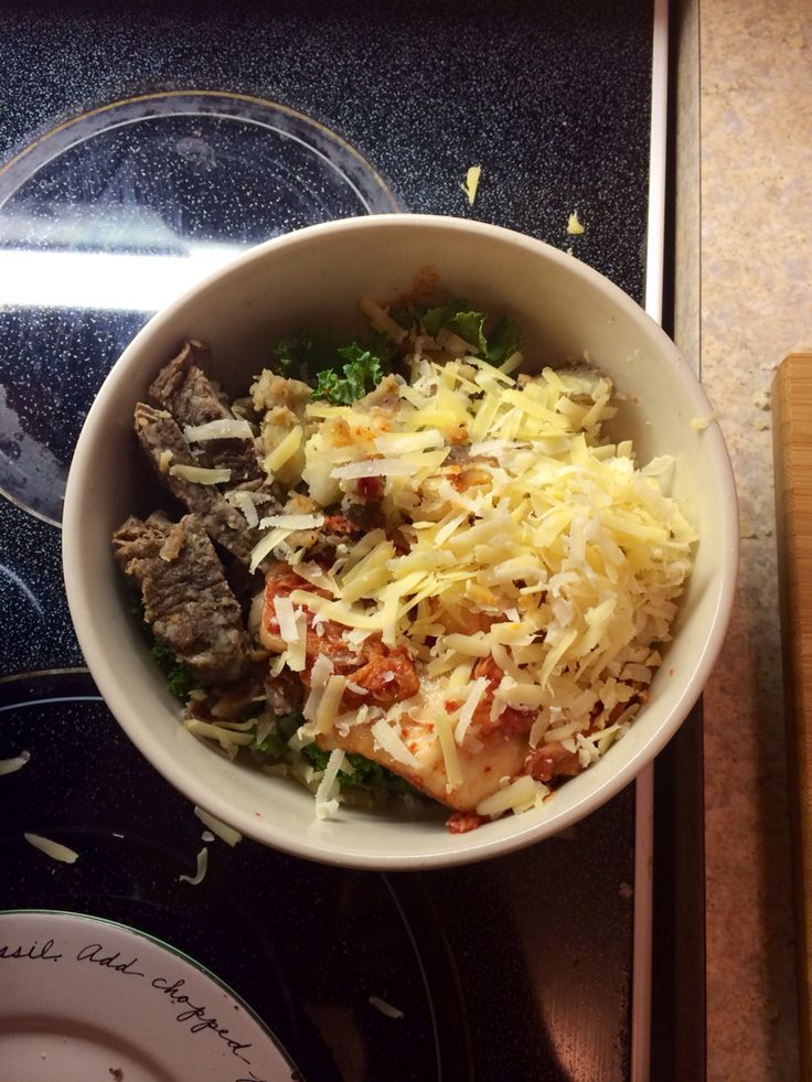 Kale bowl with steak, roasted potatoes, and kimchi topped with grated gouda and parmesan.