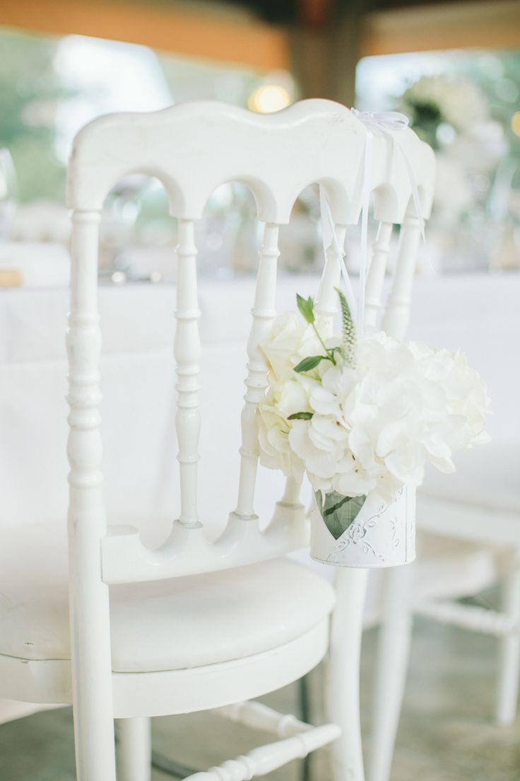 White Chair back hydrangea floral decor - Image by  M&J Photography - A destination wedding in Provence with a lace gown and groom in blue suit. White on white colour scheme. Photography by M&J Photography.