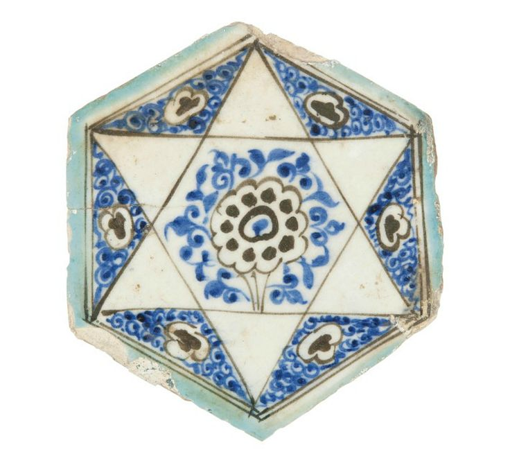 A MAMLUK HEXAGONAL POTTERY TILE  SYRIA, 15TH CENTURY  The black and cobalt-blue decoration with a six-pointed star on white ground with floral sprays and rosettes, with turquoise-blue borders 7¼in. (18.6cm.) across