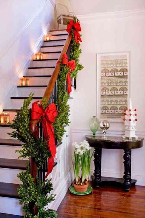 déco d'escalier pour Noël avec rubans rouges, lanternes et bougies