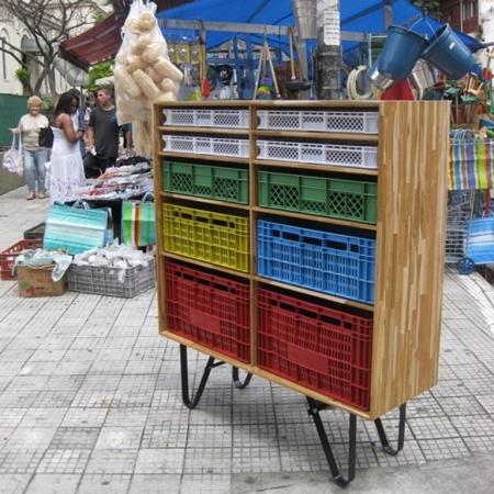 Maurício Arruda constrói estruturas de madeira certificada, com bases de aço, onde introduz as coloridas caixas de armazenamento que passam a servir como gavetas e ainda podem ser removidas da estrutura para transportar objetos