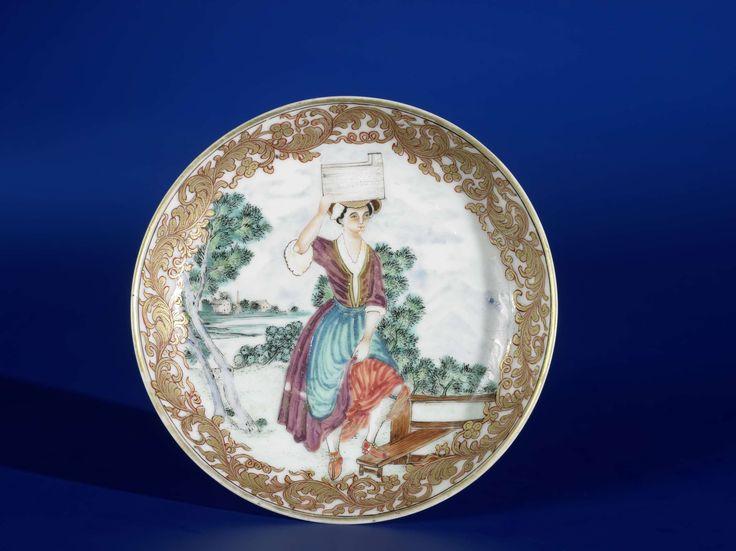 Anonymous | Schotel in emailkleuren en goud met een voorstelling van  een boerenmeisje, Anonymous, 1740 - 1760 | Schotel op een voetring, gedecoreerd in emailkleuren en goud, met een voorstelling van een meisje in een landschappelijke omgeving. Rondom een decoratieve rand.  Dit boerenmeisje wordt ook wel het Melkmeisje genoemd. Ze houdt met één hand een emmer op haar hoofd. Met haar andere hand trekt zij haar rok iets omhoog en ze staat met één been op een verhoging.  Soms is op andere…