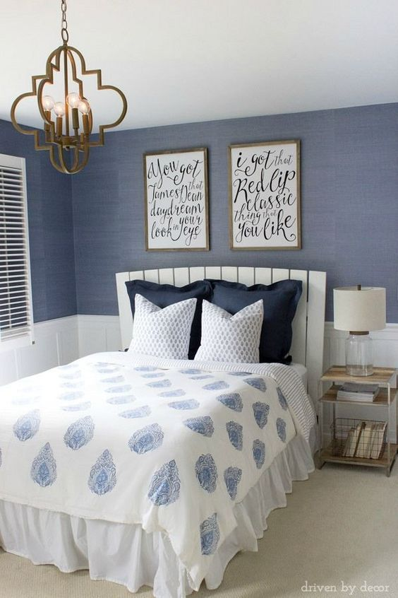 Modern coastal bedroom makeover with quatrefoil chandelier, grasscloth wallpaper, wood and chrome nightstand, and blue and white bedding. Beautiful!