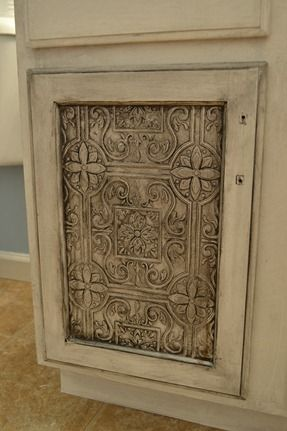Remake bath vanity door:: adhere tin tile wallpaper to the center of the doors for an entirely new look