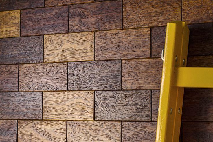 Wzór ceglanej ściany ułożony z drewnianych płytek parkietowych (merbau) / Brickwork pattern made of merbau wooden tiles.