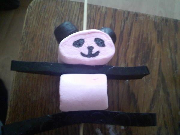 Panda traktatie! Nodig:  2 marshmallows, liefst wit, maar de roze gooi je natuurlijk niet weg  2 kokindjes  2x trekdrop  suikerwater (of glazuur)  eetbare stift zwart  saté-prikker    Werkwijze:  Kijk goed naar de foto en prik het snoep in de juiste volgorde op de saté-prikker. Plak de kokindjes als oortjes op het hoofd en teken een pandasnoet.
