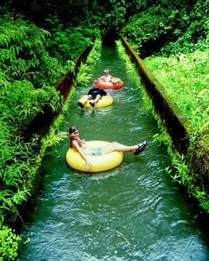 Mountain tubing adventure down the long irrigation ditches of an old sugar plantation in Kauai, Hawaii.
