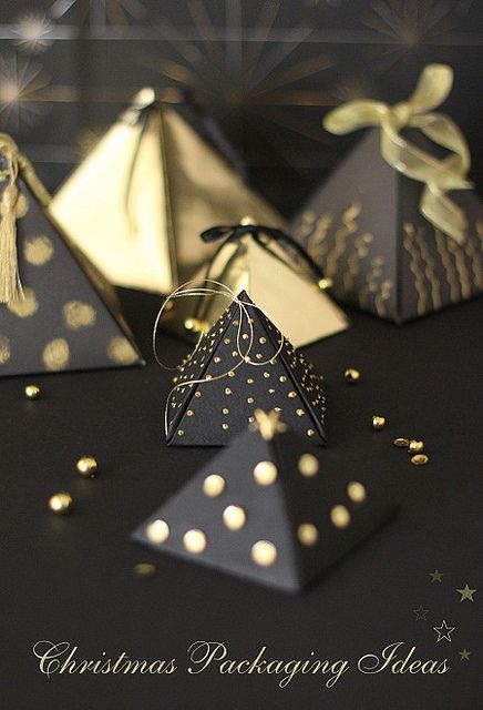 Christmas packaging ideas: paper pyramid boxes in black and gold designs ... looks like they could serve double time as tree ornaments too ...