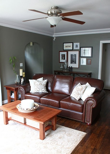 The reddish brown couch against the green gray wall Sophisticated paint colors for living room