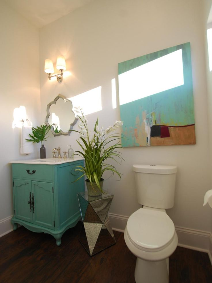 As seen on Good Bones, this small bathroom was in need of some sprucing. Once a small, dark room, Karen and Mina have transformed it into a bright, colorful space. A new coat of white paint on the walls reflects the light from the window as well as the light above the vanity, making the space feel bright, while pops of turquoise in the vanity and the artwork give the room some color. To finish off the design, a modern, mirrored plant stand gives the space a splash of personality.