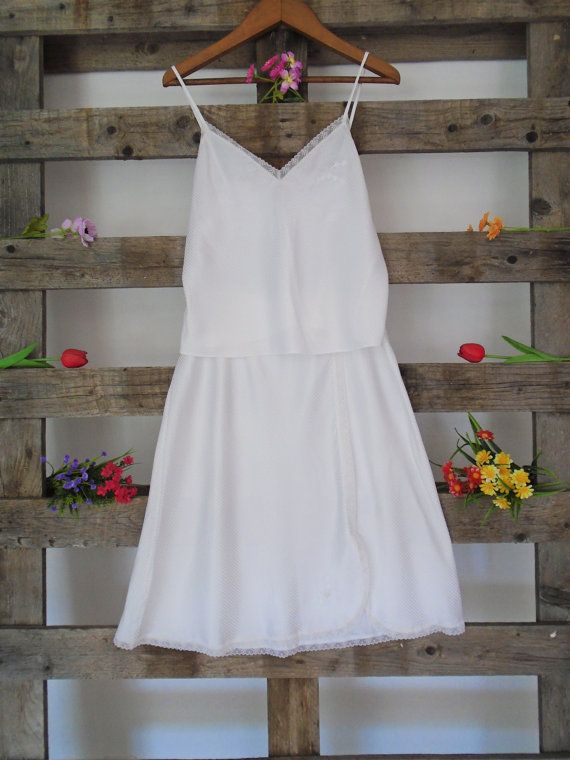 A beautifully delicate white night wear slip featuring a top and underskirt. This vintage white set has an elasticated waist and beautiful lace