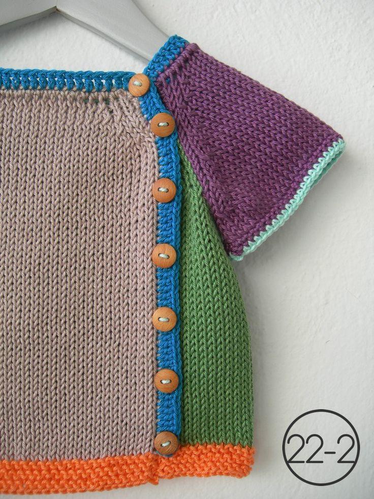 Camiseta en punto jersey con manga corta combinando múltiples colores. Elástico bajo en punto bobo y resto de remates en ganchillo. Botones de madera.
