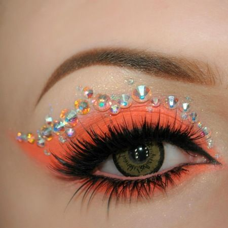 Vivid coral eye shadow with a trail of multi-sized crystals.