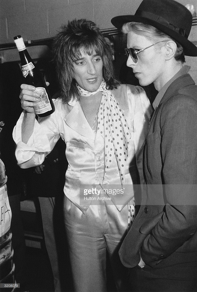 British singer Rod Stewart holds a bottle of Blue Nun wine and talks with British singer David Bowie backstage at Madison Square Garden, where Stewart performed, New York City. Stewart is wearing matching satin pants and vest, with a satin shirt and polka-dot scarf. Bowie is wearing a suit with a fedora hat and aviator sunglasses. 23rd February 1975.