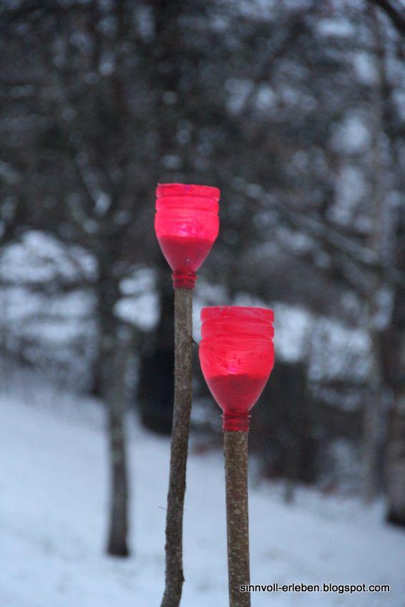 Petflasche (1L) in zwei Teile schneiden.Den oberen Teil der Flasche mit Acrylfarbe bemalen und trocknen lassen.Haselrute - in beliebiger Länge und mit einem Durchmesser, der ungefähr der Flaschenöffnung entspricht - mit einer Astschere abschneiden. Kopfüber über den Haselzweig stülpen, so dass die Öffnung den Ast fest umschließt. Wenig Sand einfüllen Teelicht reinstellen. Den Ast in die Erde (Schnee) stecken und anzünden.
