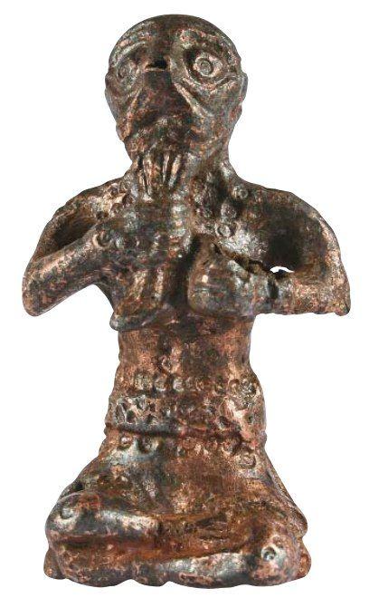 """Языческий идол. Вторая половина X века. Медный сплав, чеканка, позолота. Фигурка изображает бога Тора, который одной рукой сжимает бороду, в другой руке был не сохранившийся предмет, возможно, меч. Найден в кургане """"Черная могила"""" близ Чернигова."""