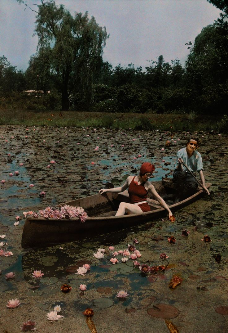 A couple in a boat paddle on a lily pond and collect flowers in the Kenilworth Aquatic Gardens in Washington D.C., 1923.Photograph by Charles Martin, National Geographic