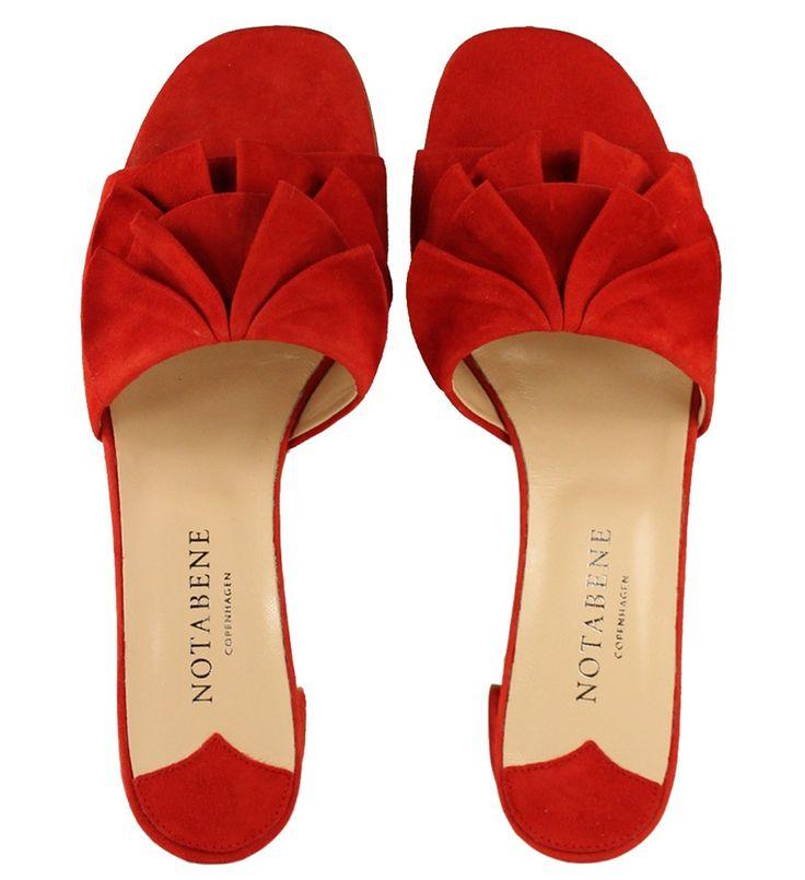 Rød sandal i ruskind med lav hæl og dekorative flæser fortil.
