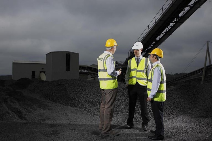 Three roadstone workers in front of a crain in quarry © David Cantwell Photography
