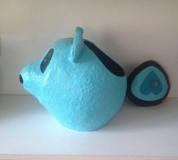 Boite ronde, artisanale en papier mâché représentant un ours. Aspect granuleux. Lobjet est peint avec de la peinture acrylique brillante bleue turquoise et noir. Le couvercle bleu est en forme de goutte sur laquelle est collée un cœur en pâte.Au centre du cœur une perle en tissu bleu et brun est fixée avec une vis; aussi, un cerné noir de 2 cm environ est placé sur le bord du couvercle. Le museau et le contour des yeux sont noirs. Les yeux sont des billes en verre de couleur verte…