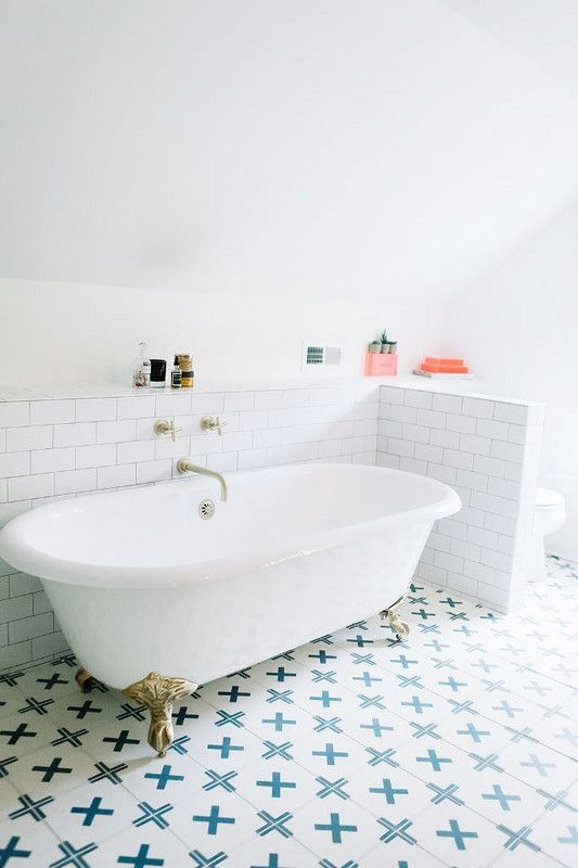 White subway tile, claw foot soaking bathtub, blue and white bathroom floor tile