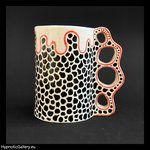 Ceramic cup painted in black spots. Ceramiczny kubek malowany w czarne cętki.