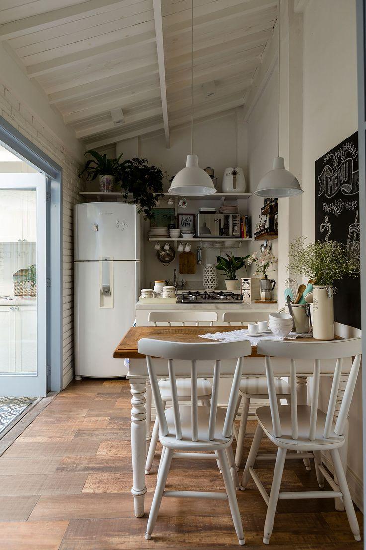 Decoração de apartamento pequeno paleta de cores em azul e branco. Na cozinha branca mesa de jantar retangular de madeira branca, cadeiras brancas, lousa e plantas para decorar.