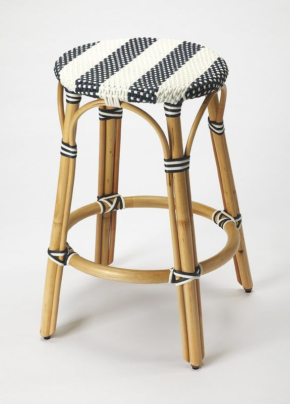 """With its distressed beige bent rattan frame and round, blue-and-white-striped acrylic seat, this counter height 24"""" bar stool is perfect for your coastal-inspired ensemble. For a casual, on-the-go dining space, pull three of these stools up to your kitchen island, then top your marble countertop with blue cotton placemats, sailboat salt and pepper shakers, and a bowl of fresh fruit for a snack on the way out the door. Or for a great place to have a cold drink on summer weekends, arrange a…"""