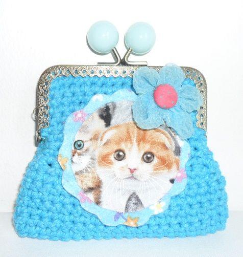 Carteira feita em linha barbante na cor azul turquesa. Fecha com fecho metálico e a decorar tem uma aplicação em feltro com a imagem de um gato. Tem ainda a decorar, uma flor em organza.  Tamanho aproximado: 10,5cm x 12cm  Preço: 5€