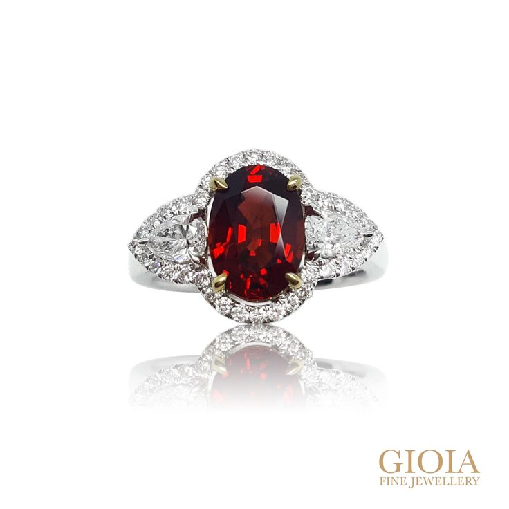 Vivid stunning red spinel, set between two pear-shaped exquisite diamonds. Hand-crafted with extreme attention in each detail, and   prong set  in natural white gold. Halo set with round brilliance diamond. Gorgeous and iconic trilogy red spinel ring, with remarkable brilliance.  Red Spinel & Ruby Shopping for a deep intense crispy cherry red ruby? It is worth considering spinel as it resembles ruby. Spinel was mistaken as ruby for its vivid red, good saturation colour until late 19th…