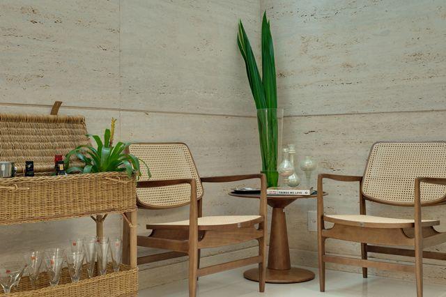Cantinho com paredes revestidas de mármore travertino + móveis de madeira, vime e palha. Projeto Anna Paula Melo.