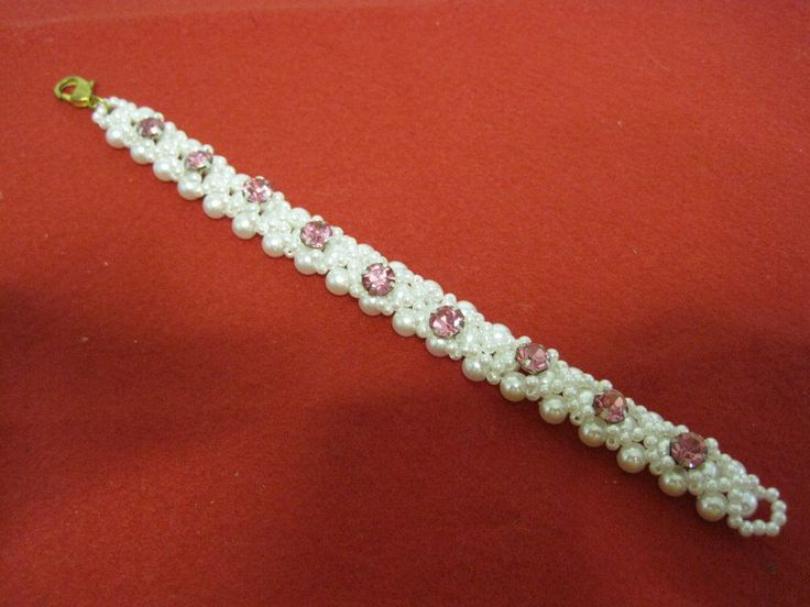Bracciale in perle bianche con finizioni in cristallo rosa, chiusura a moschettone.