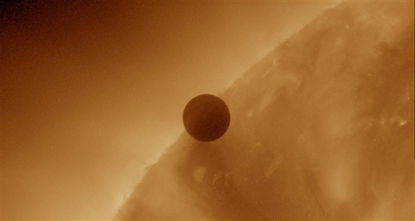 An image from NASA's Solar Dynamics Observatory shows the planet Venus in the midst of crossing over the edge of the sun's disk, as seen from Earth, at the beginning of its last-in-a-lifetime transit.