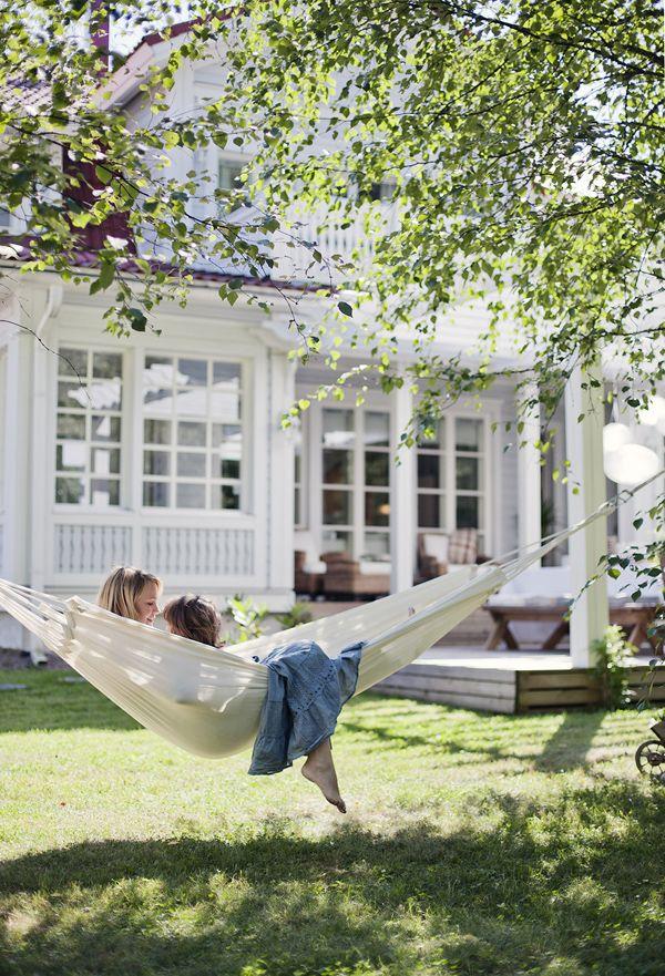 Hängmatta, sommar och barn. Ett vackert hus med stora fönster.