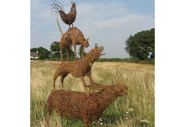 A willow statue of the classic image from the Brothers Grimm fairy tale about the Town Musicians of Bremen. Made from willow it contains a lifesize donkey, dog, cat and cockerel.