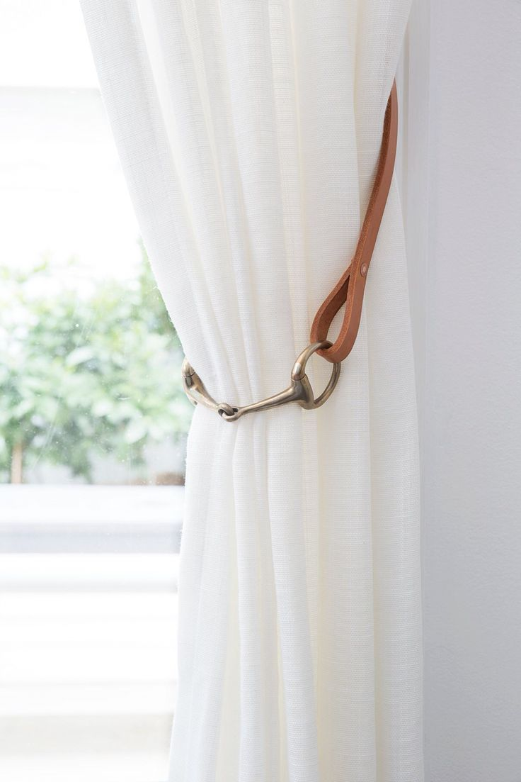 Curtain Tiebacks by Shakespeare Design. The stunning natural beauty of tan leather coupled with a brass horse bit adds texture and a stunning feature to sheer white linen curtains. Enquiries to www.shakespeare-design.com.au
