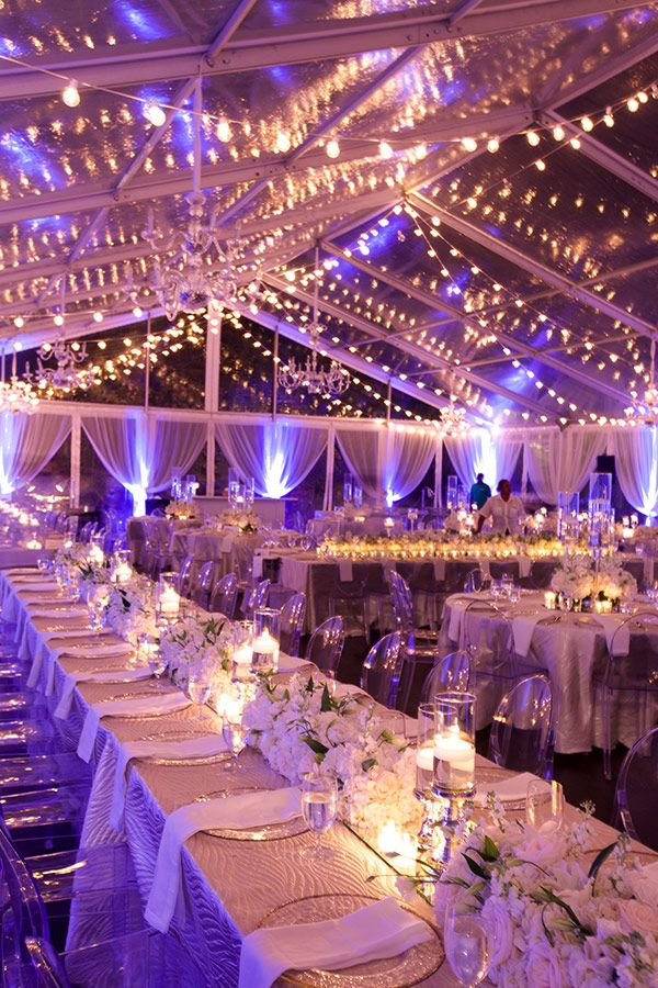 A festa de casamento de Mica Rocha e Renato Mimica nas Bahamas: salão transparente com fios de luzes pendurados estilo americano, mesas infinitas com cadeiras de acrílico e decoração essencialmente branca com toques de verde.
