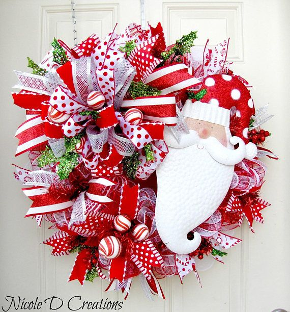 This Santa mesh wreath will look fabulous on your front door or hanging on your wall this holiday season! It is full of gorgeous wired ribbon and an adorable metal Santa face that will for sure brighten anyones day! This wreath is made using deco mesh loops inn red and white. I also