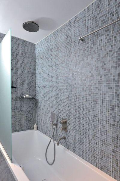 """Bain ou douche, au choix  En acier émaillé, comme la vasque, la baignoire-douche """"Conoduo"""" (Kaldewei) occupe toute la longueur de la pièce. Utilisable pour le bain ou la douche, elle accueille en effet une haute pomme ronde. L'espace est fermé par une paroi en verre dépoli, qui protège des éclaboussures et offre un peu d'intimité."""