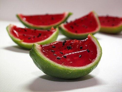 """1)taglia a metà dei lime   2)prepara una gelatina e colorala con colorante alimentare rosso  3) versa la gelatina dentro le metà dei lime  4)quando sarà solidificata taglia in spicchi le """"ciotoline""""   5)crea i semi con semini di papavero o sesamo"""