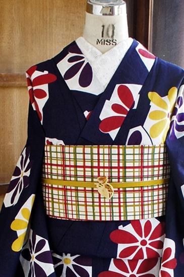 濃紺の地に、光のかけらのような白の六角形と、紫、黄色、赤のカラフルお花模様が染め出された、レトロキュートな注染浴衣です。