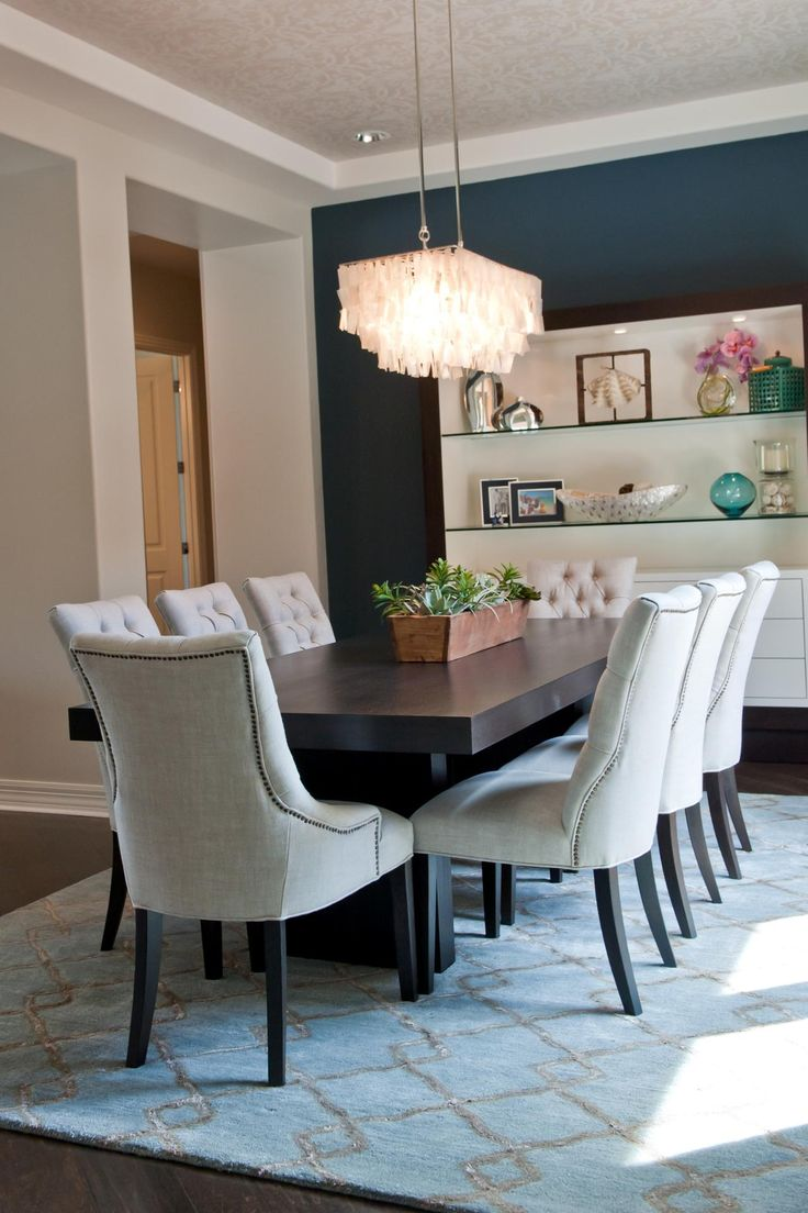 Eight off-white tufted chairs surround a dark wood table in this chic transitional dining room. A dark blue accent wall attracts the eye to the built-in shelving that displays picture frames and art. Above the table, a fun rectangular chandelier adds light to the space.