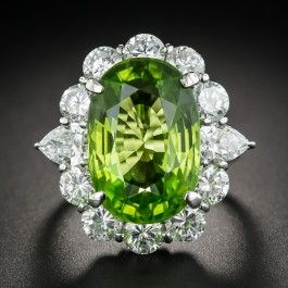 "A large (12.90 carat) and luscious, vibrant apple green, faceted oval Peridot glistens and glows from within a sizable sizzling halo composed of no less than 4.43 carats of bright-white and sparkling round brilliant-cut diamonds punctuated by a pair of half-carat each pear shape diamonds at the shoulders. Measuring just under one inch (15/16""), this impressive high quality estate bauble is rendered in gleaming platinum. A head turner! Currently ring size 6 3/4."