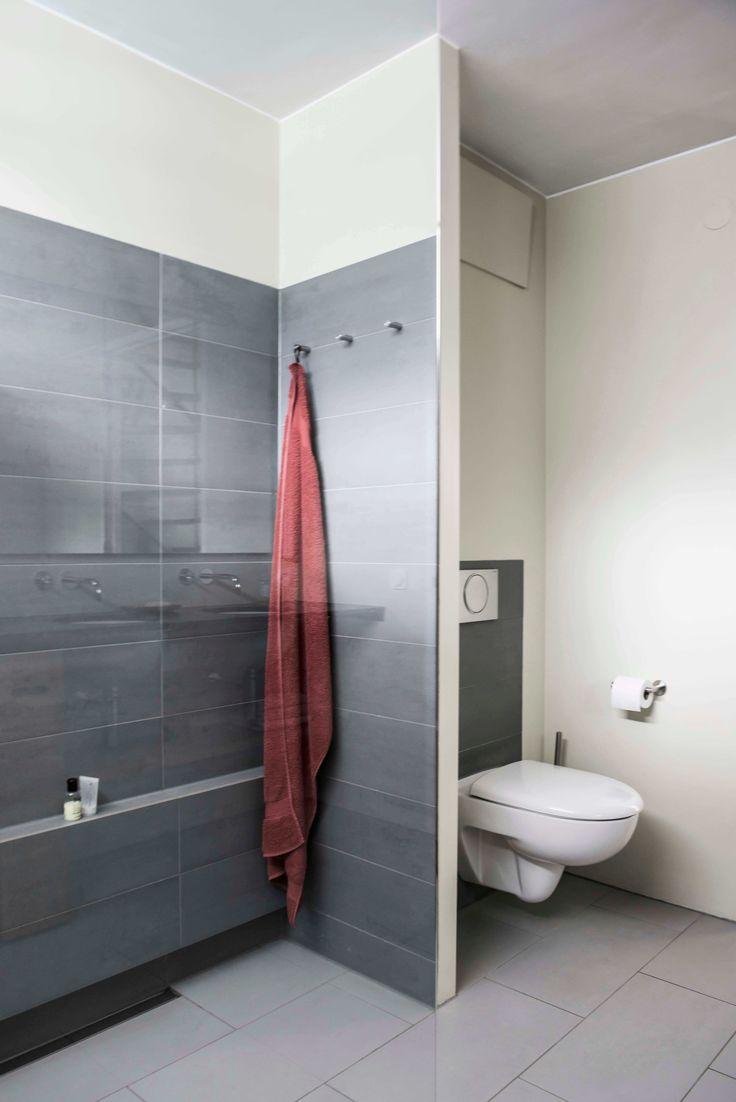 Het muurtje waar je handdoeken kunt ophangen camoufleert de leidingskoker achter de wc.