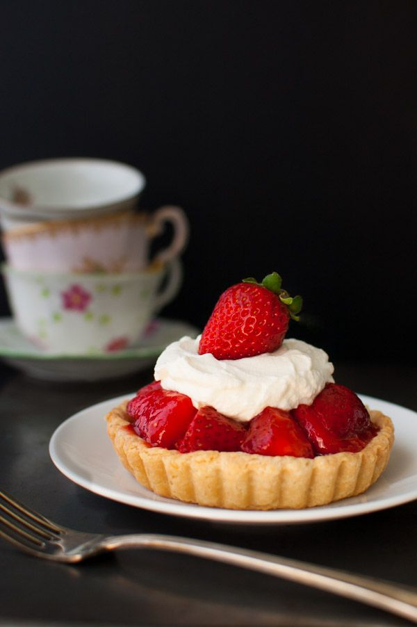 Individual Fresh Strawberry Pies - individual sized mini-pies with strawberries lightly sweetened with a fresh strawberry glaze topped with whipped cream in a flaky, buttery pie crust from tamingofthespoon.com