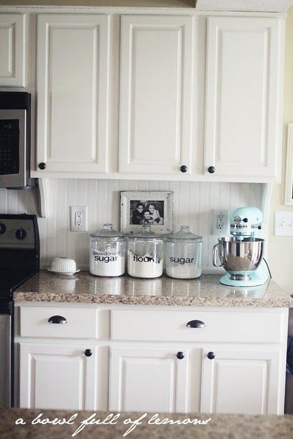 Canisters With Dicut Letters, Color Of Countertop, White Cabinets, Beadboard  Backsplash, Corbels